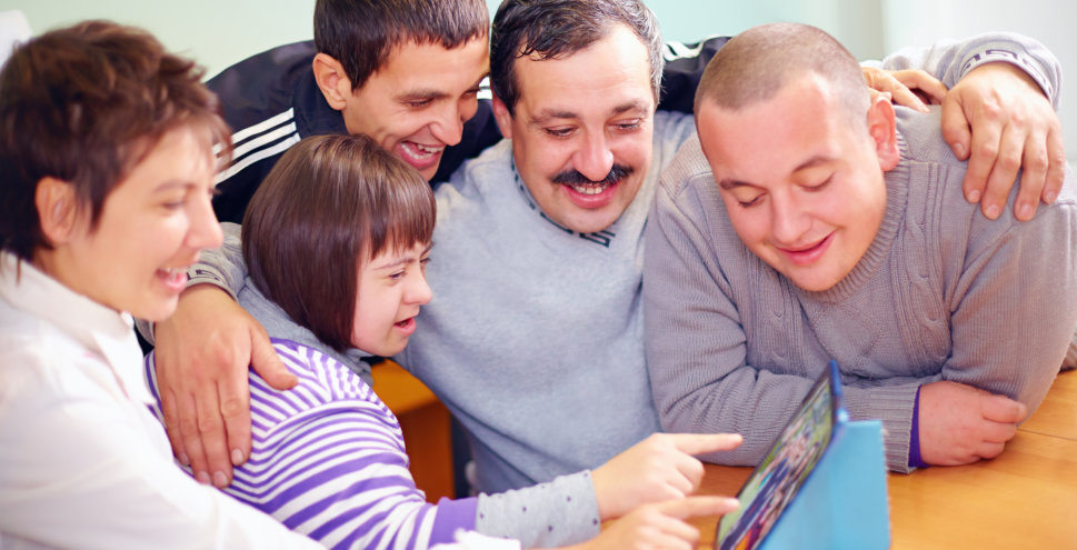 The men are teaching the little girl how  to use the tablet