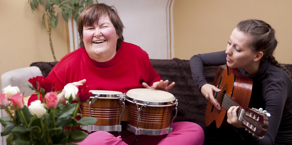 the woman is happily playing the drum